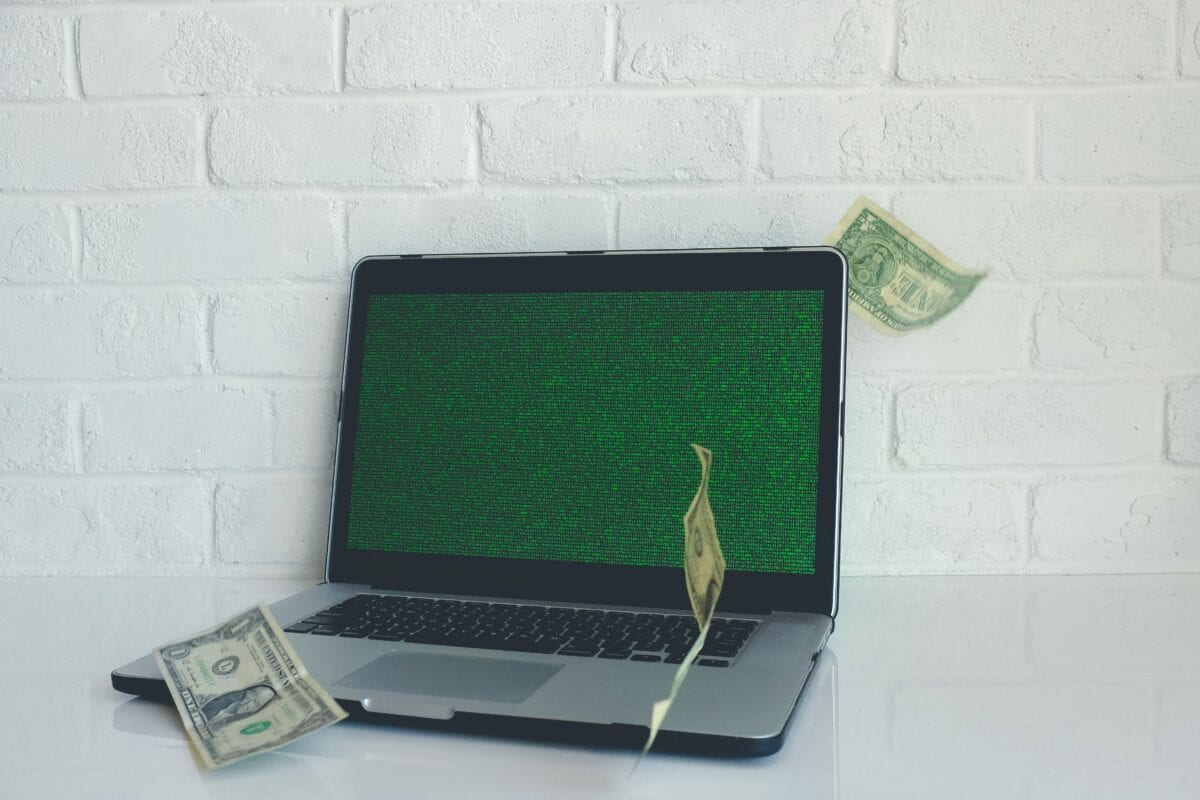 An open Apple laptop showing code on the screen with three floating dollar bills.
