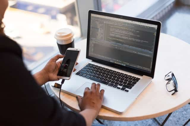 alt= [Image of a person editing code with coffee.]