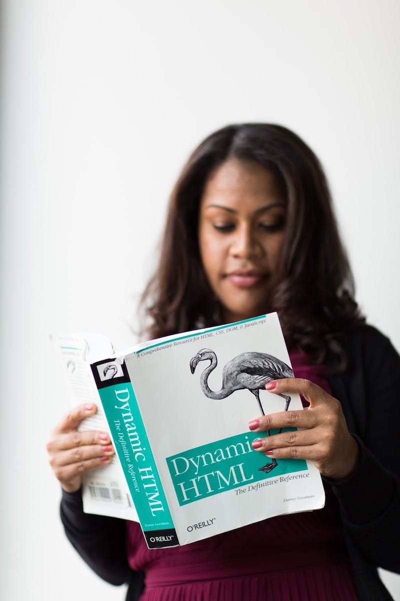 Image of woman reading Dynamic HTML textbook.