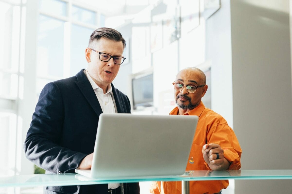 Image of men collaborating around a computer.