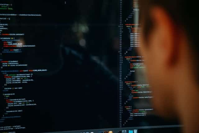 [Image of a person looking at code on a computer screen.]