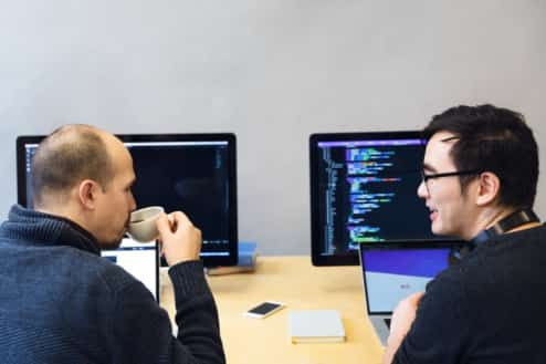 Two guys talking in front of a computer