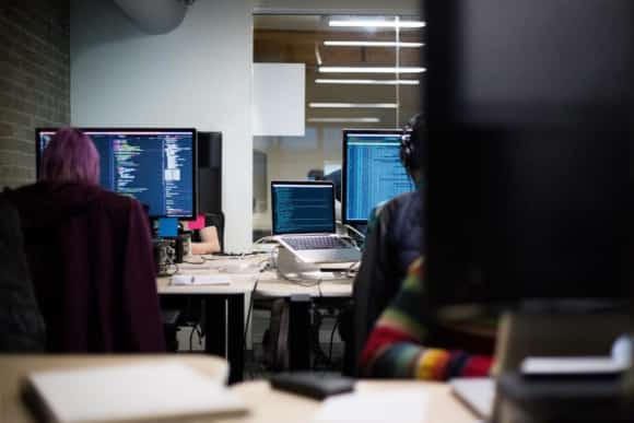 image of people coding in an office