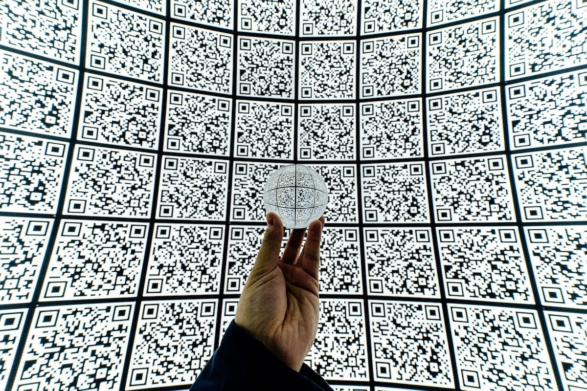 Person holding clear glass ball with QR code background""