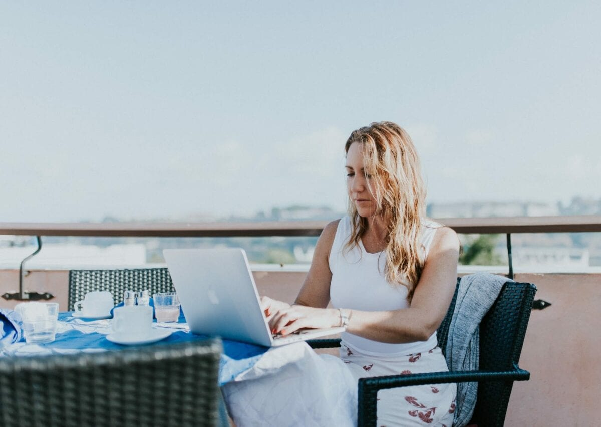 Image of woman working on a computer at a waterfront cafe.