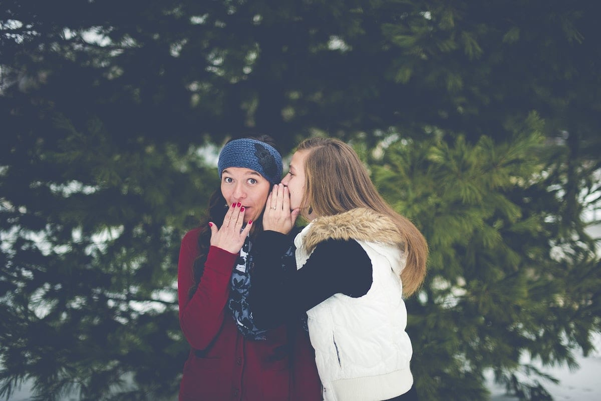 """Picture of two women sharing a secret."""