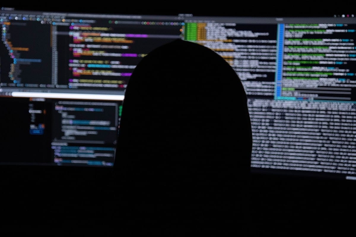 A person coding in a dark room.