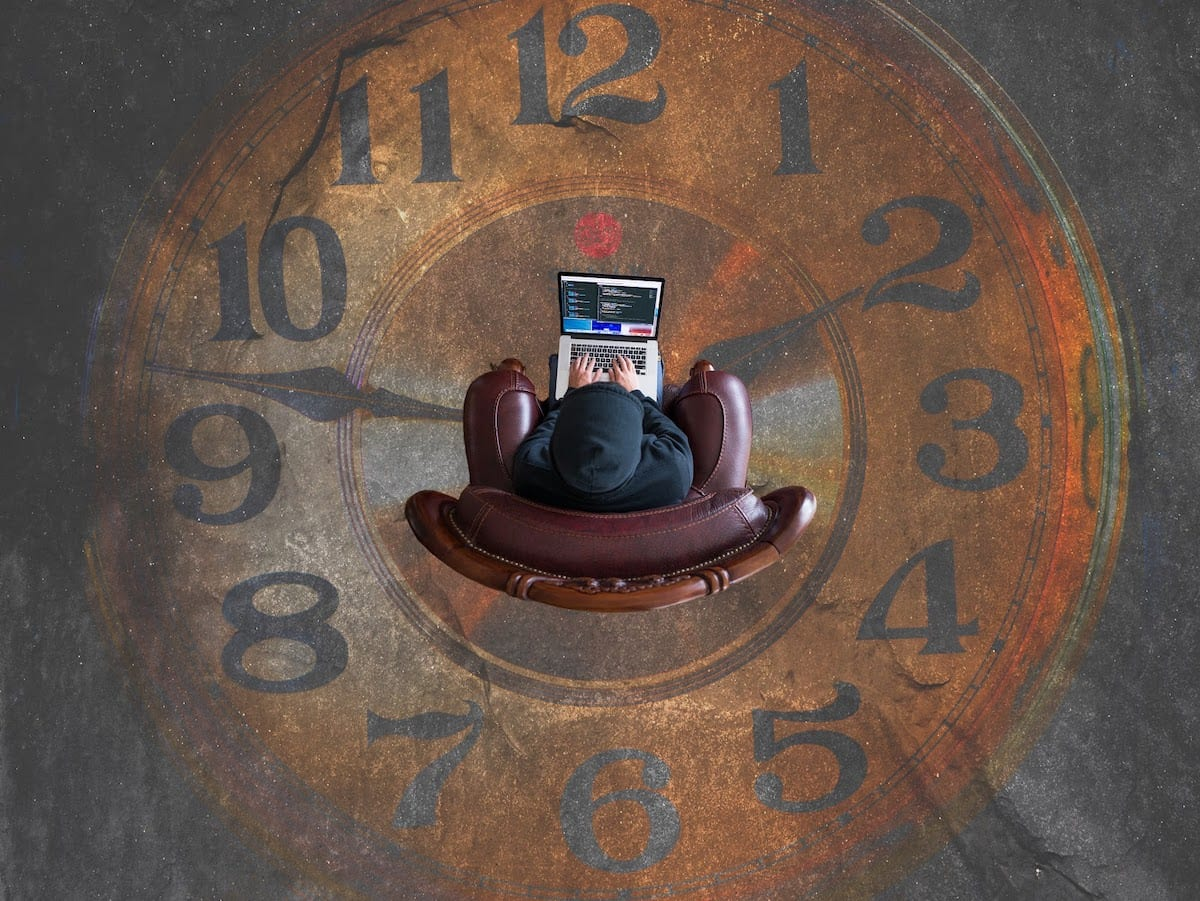 Image of a coder sitting on a clock painting.