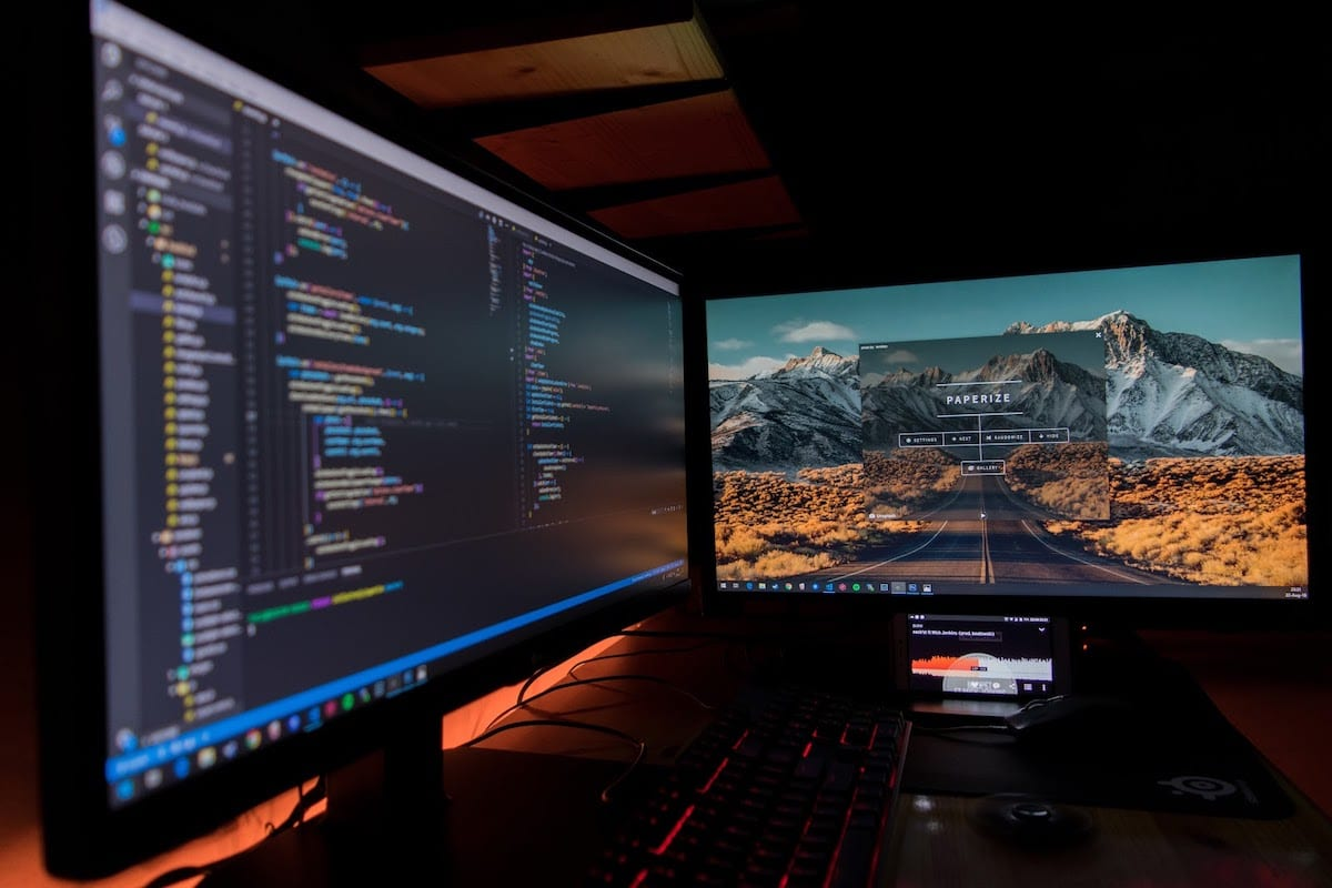 Two monitors with code on display
