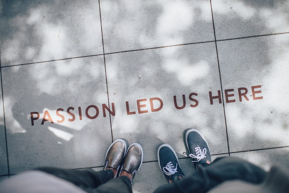 """People standing over a message written on the sidewalk, reading """"Passion Led Us Here."""""""