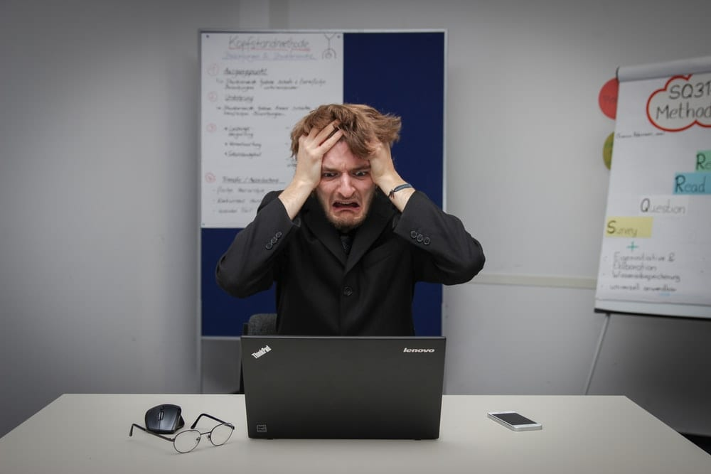 Frustrated man using computer.