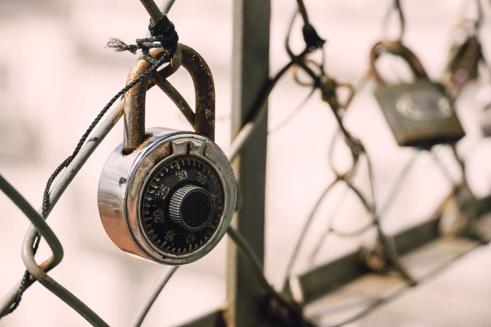 Image of a combination lock on a fence.
