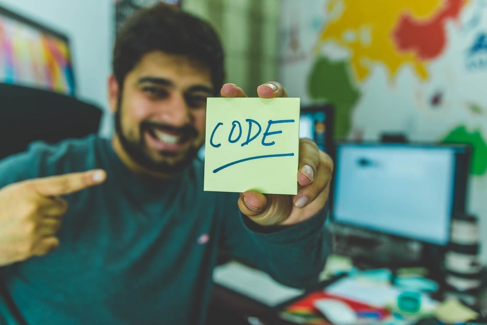 A person pointing at a note with 'code' written on it.