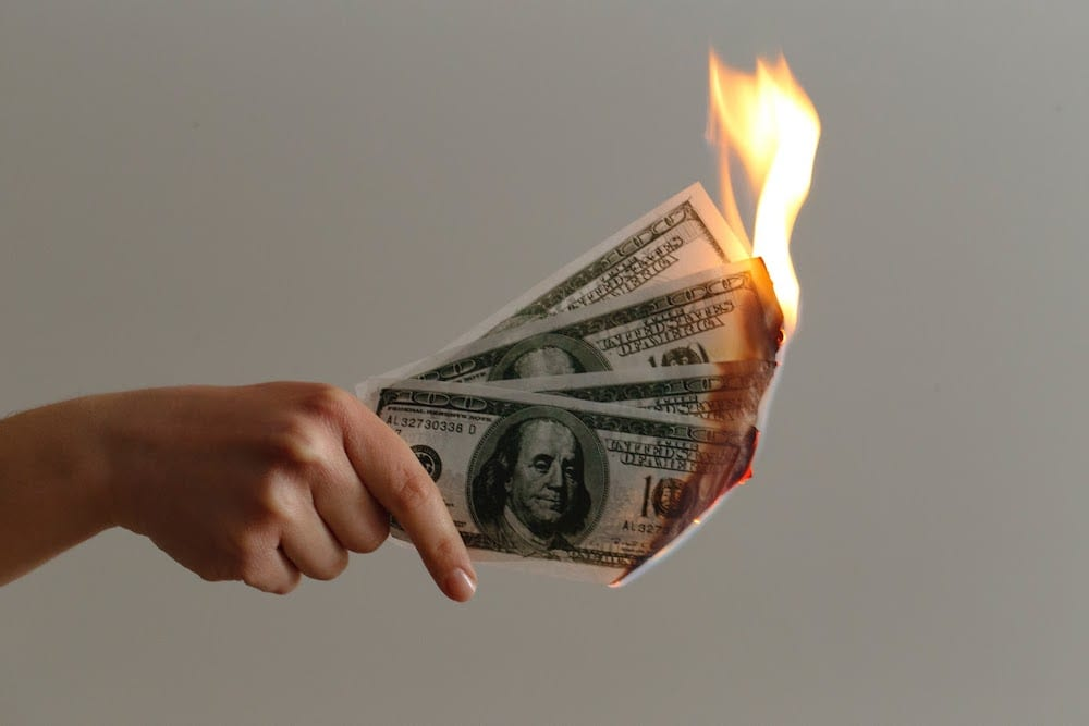 Burning hundred-dollar bills
