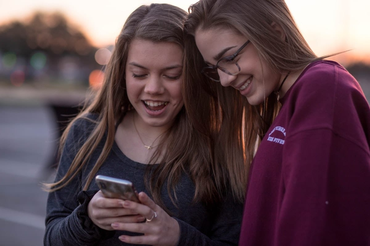 two girls looking at a phone