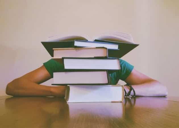 person studying behind stack of books