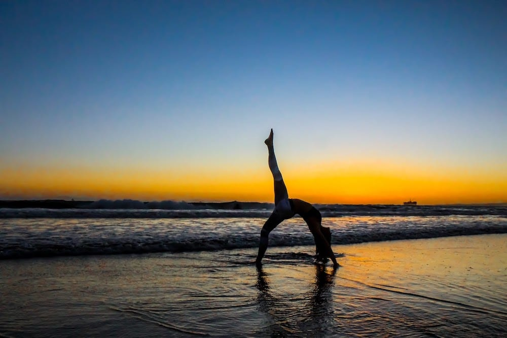 A person doing yoga on a beach.