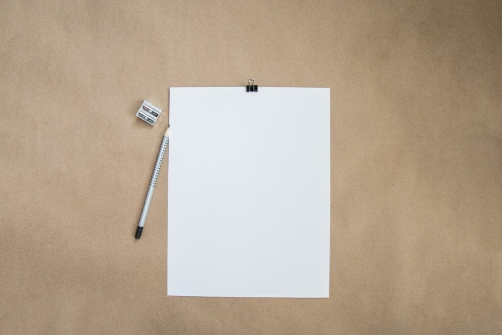 A stark, blank page with a pencil and pencil sharpener on a table.