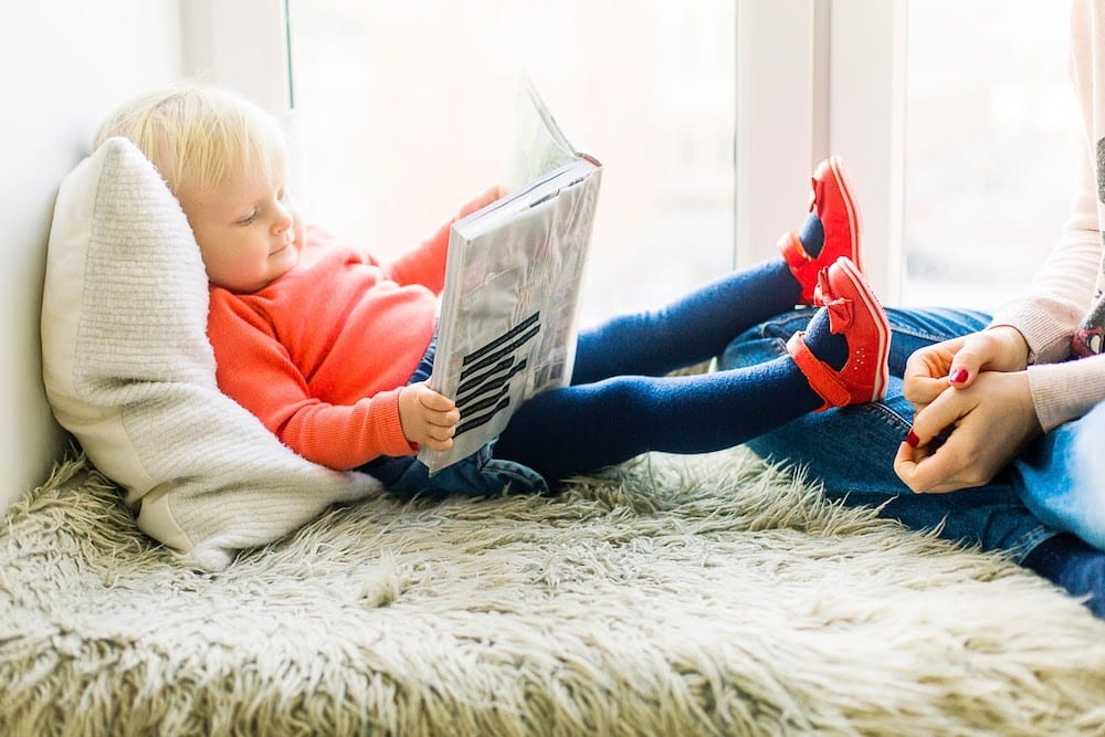 A young child reclining comfortably and reading a book.