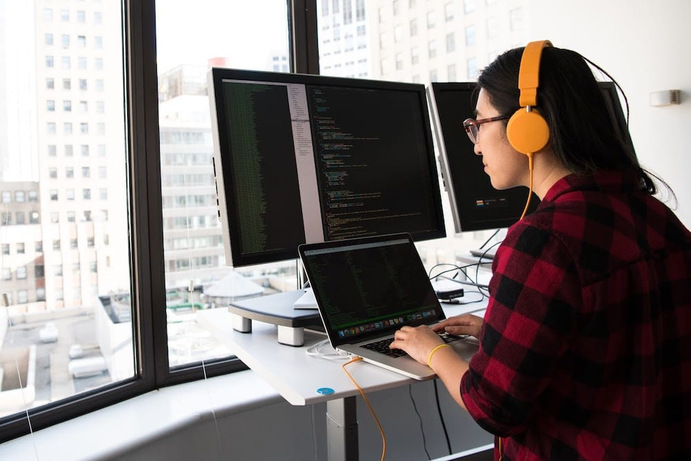 A person coding at a computer workstation
