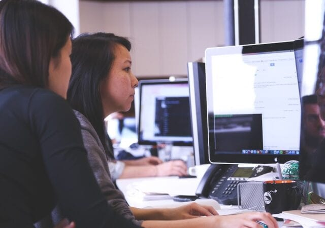 two women working on a project on a computer