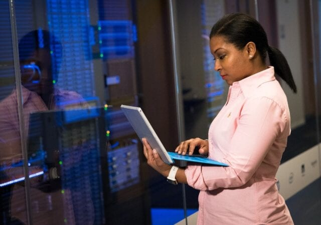 A woman in a pink button up uses a laptop while standing in front of computer hardware.