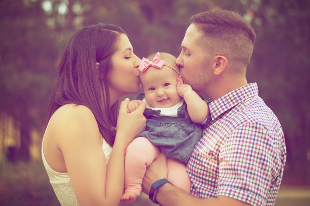 Parents kissing a baby