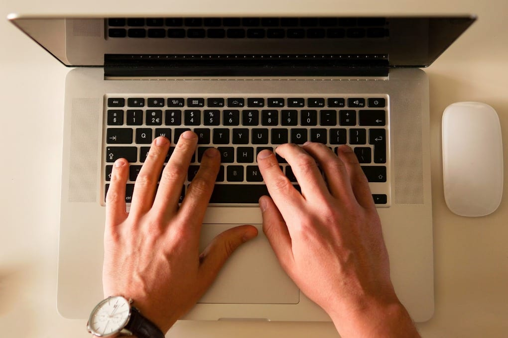 Overhead shot of hands typing on a computer