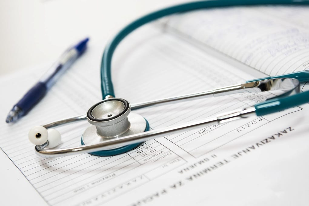 A stethoscope and a pen on a report