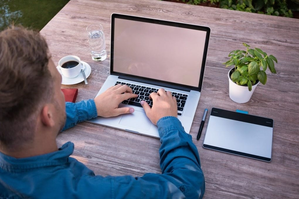 man typing at laptop with coffee and tablet