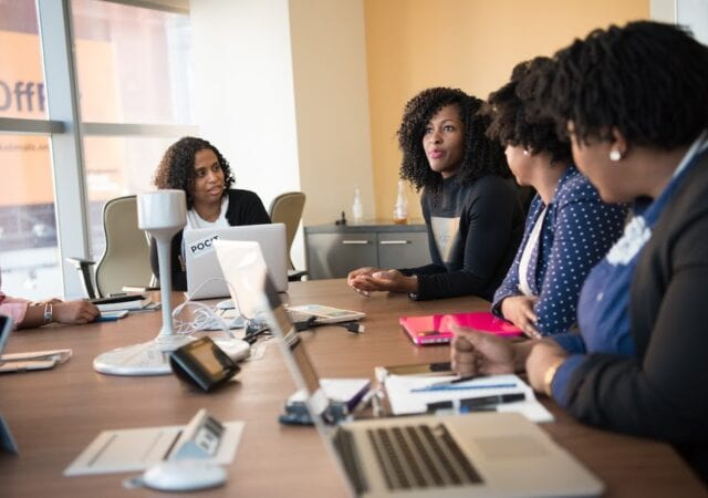 A group of four women discussing business solutions.