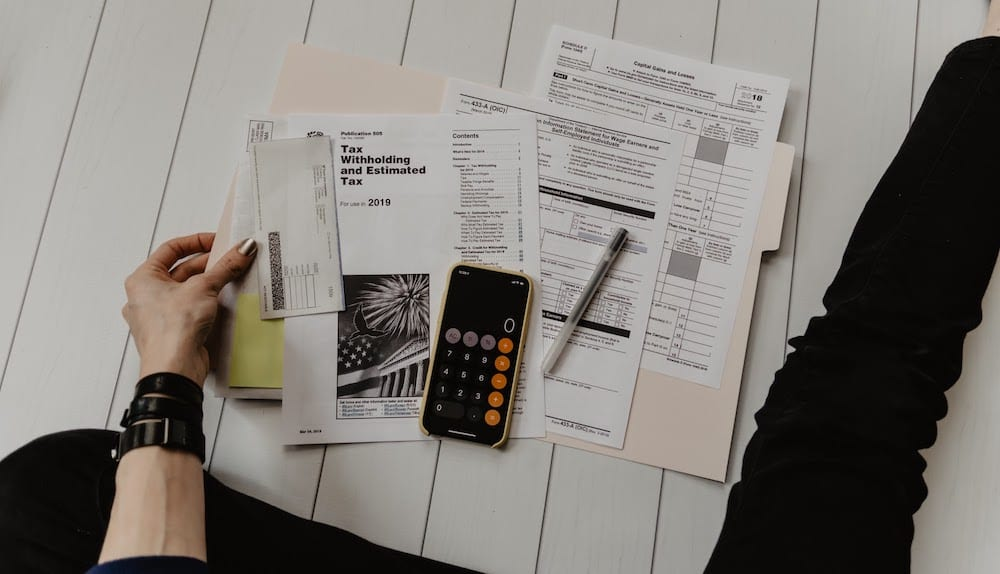 Tax documents open on a beige folder with a phone calculator and pen