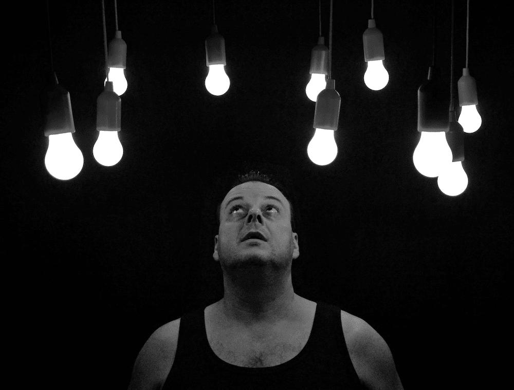 A person looking up at a number of lit bulbs in a darkened room.
