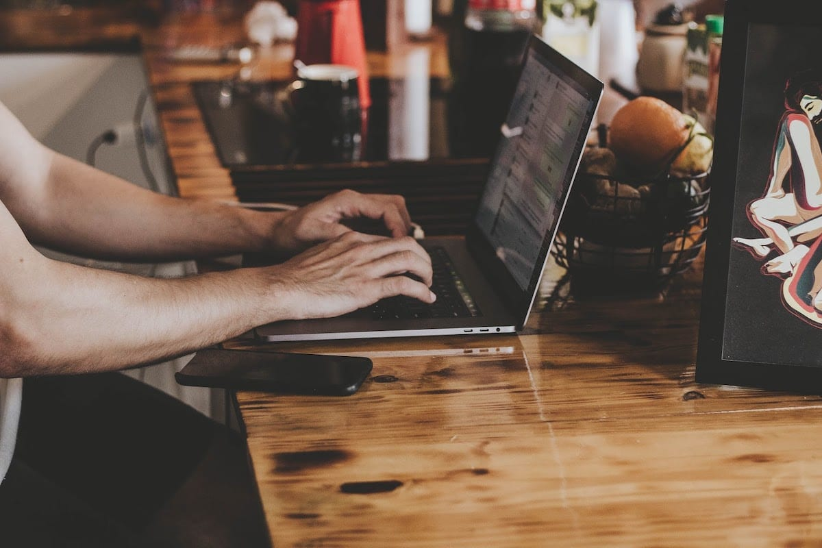 Person In Front Of Laptop On Brown Wooden Table 2115217