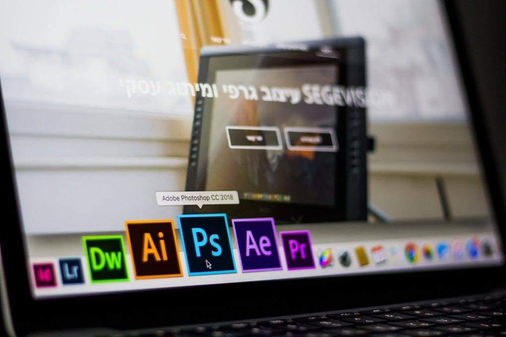 A laptop screen showing Adobe applications