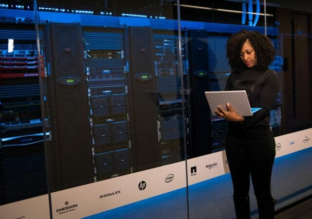 A woman is standing while carrying a laptop outside a network administration bank of servers.