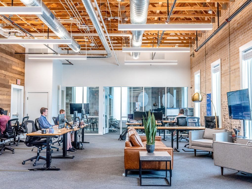 A photo of an office with people working at their desks.