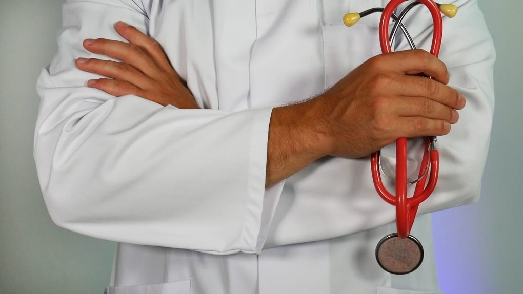 A person in lab coat holding a stethoscope