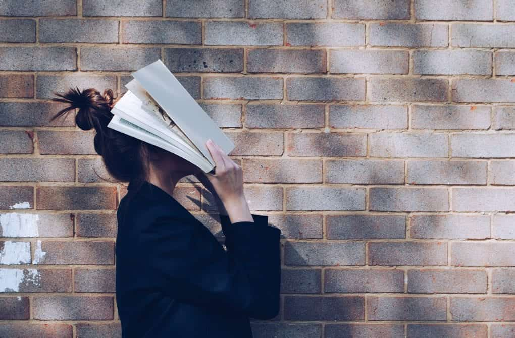 A person holding a book to their face.