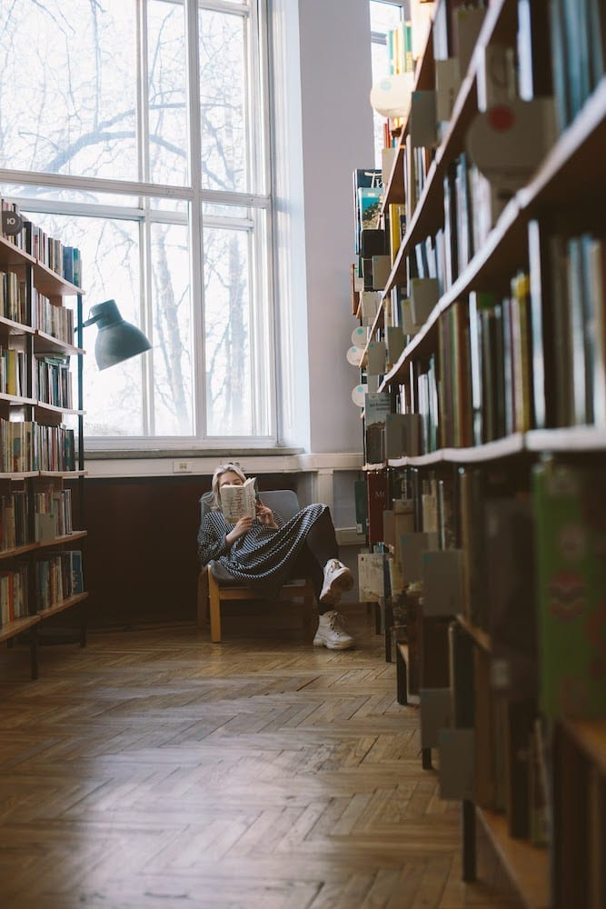 A person reclining in a library with a book.
