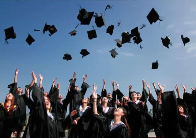 University students throwing caps into the air at a graduation ceremony
