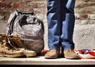 A person standing next to a pair of boots and a camo backpack
