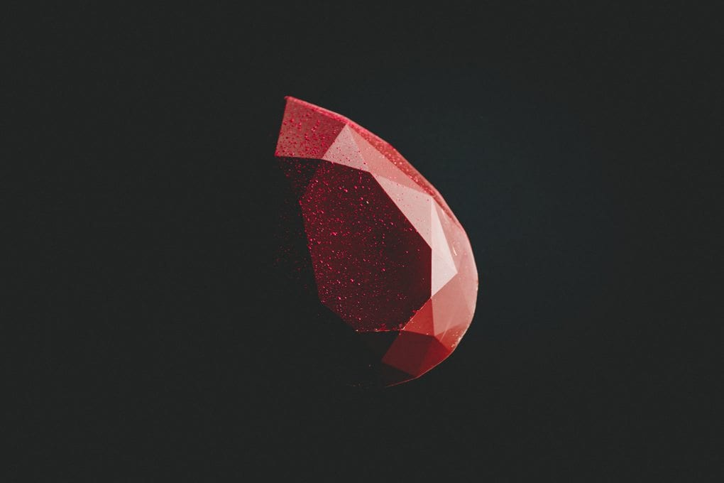 Faceted red gemstone in the dark.