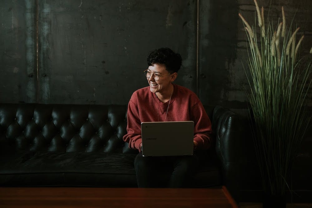 A woman in glasses and red sweater smiling while a laptop is resting on her lap