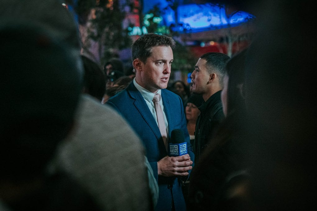 man reporter speaking in a crowd