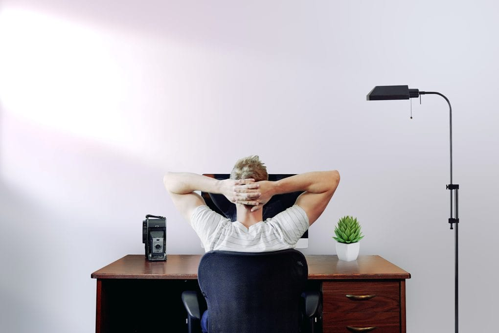 Man sitting at desk in front of computer with arms stretched behind him and hands resting on head