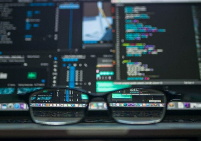 close up of glasses with computer workstation