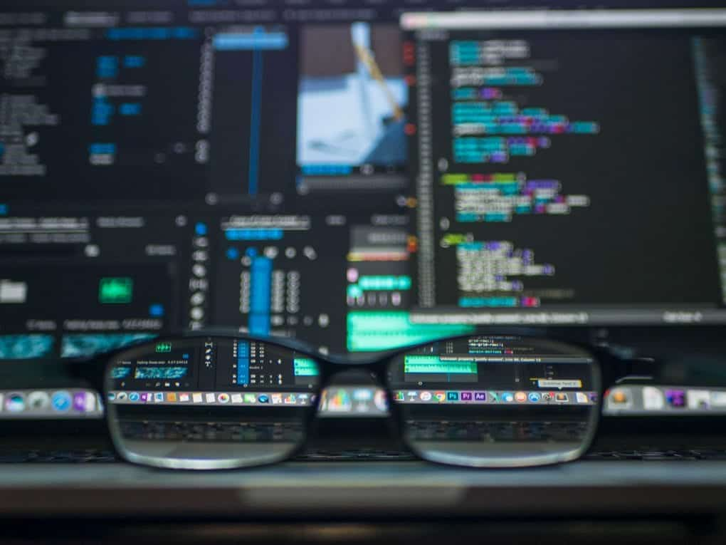 A desk displays glasses in the foreground and several screens in the background displaying technical code