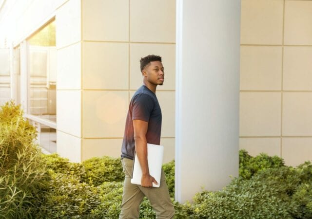Young man walking toward building with laptop in hand