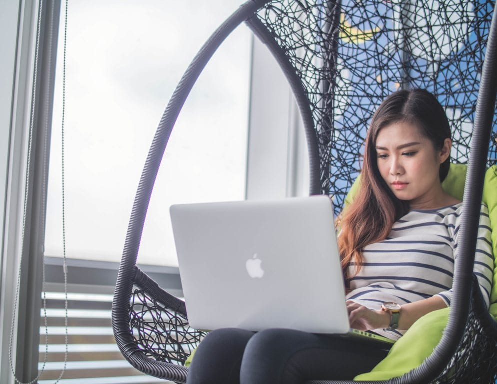 A girl sitting in a wicker chair with a green cushion while working on her computer near a window.